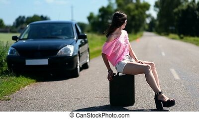 Lovely woman sitting on canister on country road - Lovely...