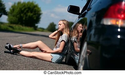 Blonde girl sitting on road near her broken car - Blonde...