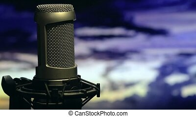 Isolated microphone on stand background cloudy sky in the...