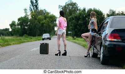 Young women hitchhiking near broken car - Young sexy females...