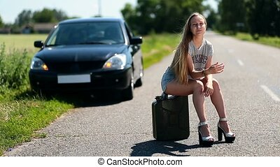 Upset sexy girl sitting on rusty canister on road - Upset...