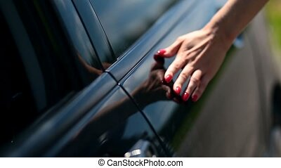 close up of woman's hand sliding on car surface