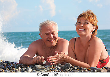 happy aged pair lie on pebble beach, focus on man, woman in...