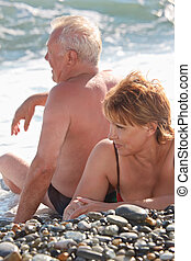 aged pair sit on pebble beach