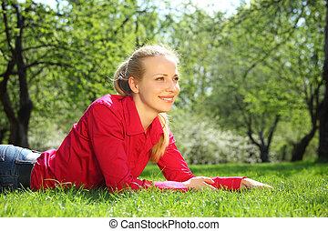 beautiful blonde lies on grass in garden in spring