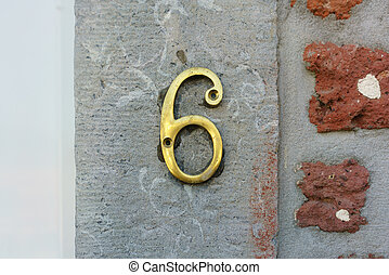 Number 6 - Brass house number six on a stone wall