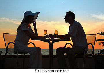 Female and mans silhouettes on sunset sit at table with two...