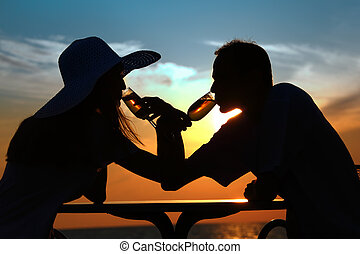 Female and mans silhouettes on sunset behind table drink...