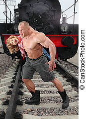 strong shirtless man saving little girl on railroad