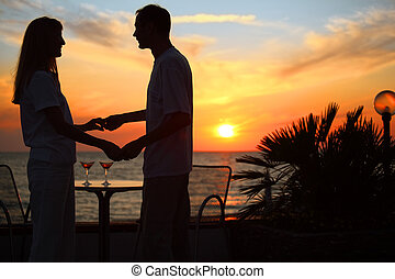 woman and man keep for hands against sunset on  sea