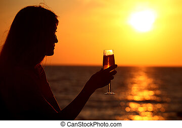 Female silhouette on sea sunset with  glass in hand