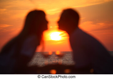 Blurred female and man\'s silhouettes on sunset sit at table with