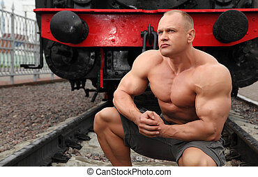 strong shirtless man sits on railroad against locomotive
