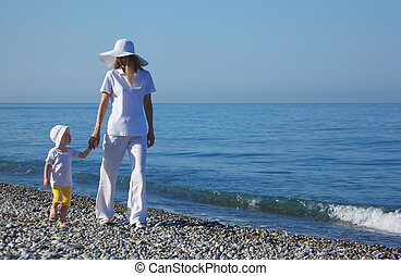 Mother with child walk on edge of sea