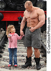 strong shirtless man stands on railroad with little girl...