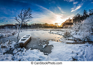 Old boat on the lake covered with snow in winter