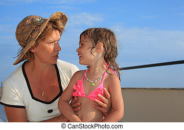 mature woman with little girl on veranda