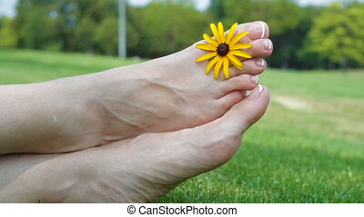 Relaxing pedicure and manicure with a yellow flower