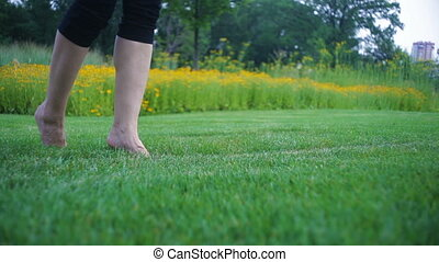 beautiful young woman running barefoot on grass in the...