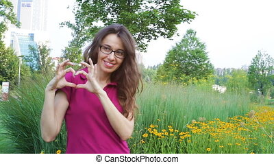 Outdoor portrait of young beautiful fashionable woman posing near flowers