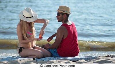 pretty woman applying sunscreen on man's shoulder - Pretty...