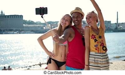 Group of smiling friends making selfie on beach