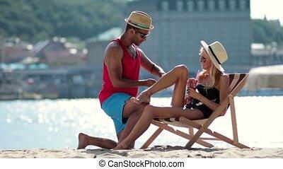 man applying sunscreen on girlfriends leg on beach