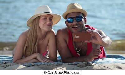 Happy couple making a selfie with phone on beach