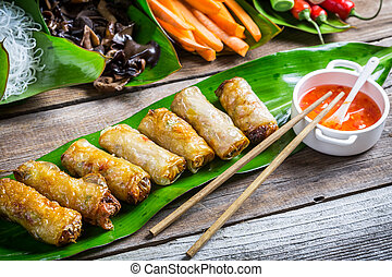 Fried spring rolls surrounded by ingredients