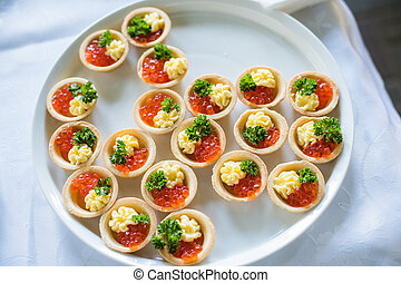 Red caviar with bread on black on a white plate