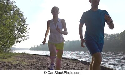 Super slow motion video of athletic girl and man running together towards the camera against sun