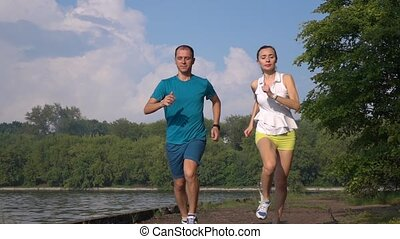 Slow motion video of tired girl and man running together towards the camera
