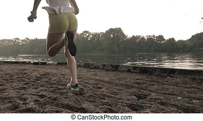 Athletic girl's legs super slow motion video. Running on...