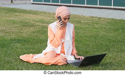 Arab business woman on the mobile phone in a park with a...
