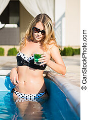 Slim young blonde posing in the swimming pool with a drink