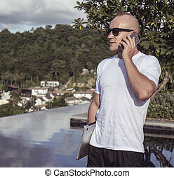 Outdoors portrait of handsome young man talking on the...