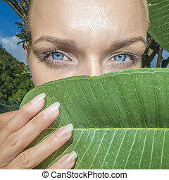 Closeup of pretty blonde woman's blue eyes with tree leaves on a sunny day
