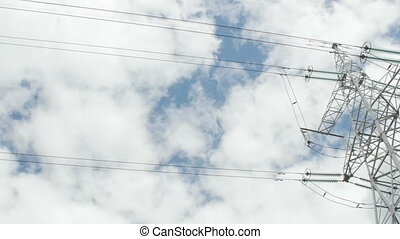 High voltage towers with cloudy sky background.