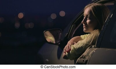 Thoughtful woman enjoying landscape of night city from open...