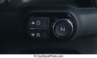 Woman hand pushing reverse gear button in car - Close up...