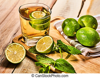 Glass with green lime drink and mint napkin. - Alcohol...