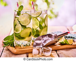 On wooden boards is glass with mohito and scoop ice. -...