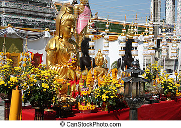 Buddhist shrine with Buddha statues, flowers and offerings