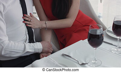 Young man and woman on romantic dinner drinking at restaurant, celebrating valentine day.