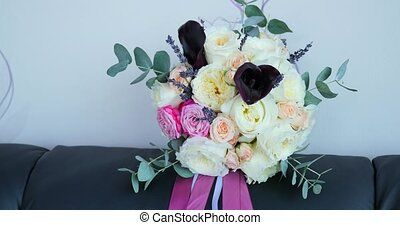 bridal bouquet on a black couch.