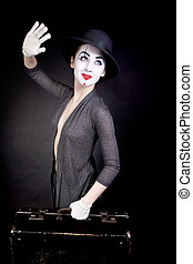 Female mime in white gloves with a suitcase