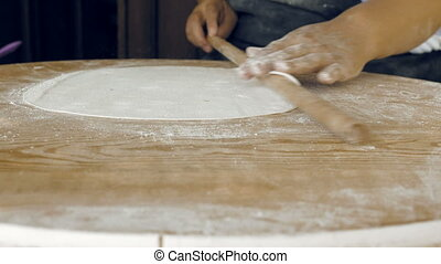Rolling the pastry dough on a flat wooden surface - A woman...