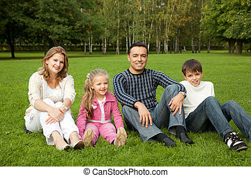 happy family of four persons outdoors