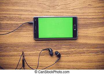 Smart phone with green screen on wooden table background