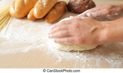 Kneading the dough on the table full of flour.